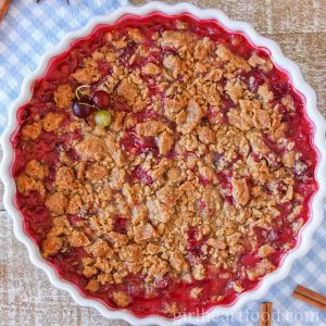 Dish of gooseberry crumble on a blue and white checkered cloth.