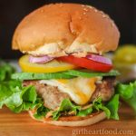 Ground turkey burger with cheese, lettuce, tomato, onion, avocado and sauce.