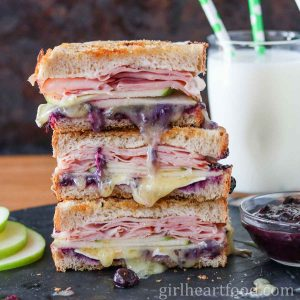 Three grilled ham and Brie sandwiches stacked on top of each other next to apple slices, dish of jam and milk.