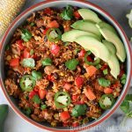 Large round dish of a chicken and rice skillet garnished with avocado, cilantro and jalapeno.