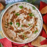 Large bowl of homemade onion dip garnished with caramelized onions and parsley and next to tortilla chips.