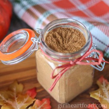 Jar of homemade pumpkin pie spice with a ribbon tied around it.