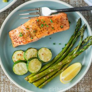 A fillet of honey mustard salmon with vegetables and lemon wedge on a blue plate.