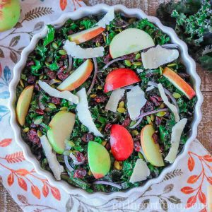 Bowl of raw kale and apple salad with shavings of Parmesan over top.