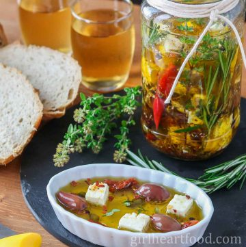 A jar of marinated feta cheese alongside bread, wine, herbs and a small dish of the oil marinated feta.