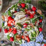 Large bowl of mixed green salad with fruit and homemade poppy seed dressing.