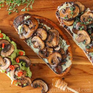 Three slices of mushrooms on toast sitting on a wooden board next to a honey stick.