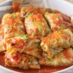 Old fashioned cabbage rolls piled on a plate with tomato sauce and garnished with dill.