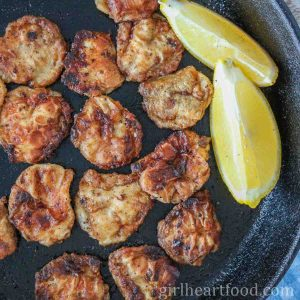Pan-fried cod tongues and two lemon wedges in a cast-iron skillet.