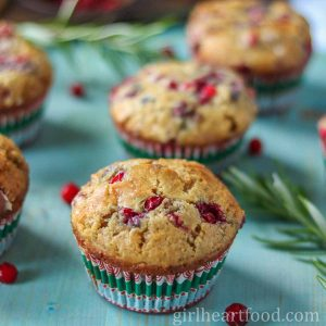 Partridgeberry muffin on a blue platter next to partridgeberries and rosemary sprig.