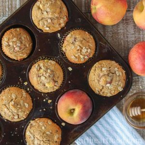 Peach muffins in a muffin pan alongside fresh peaches and dish of honey.