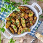 Small white dish of roasted fingerling potatoes with pesto garnished with parmesan and parsley.