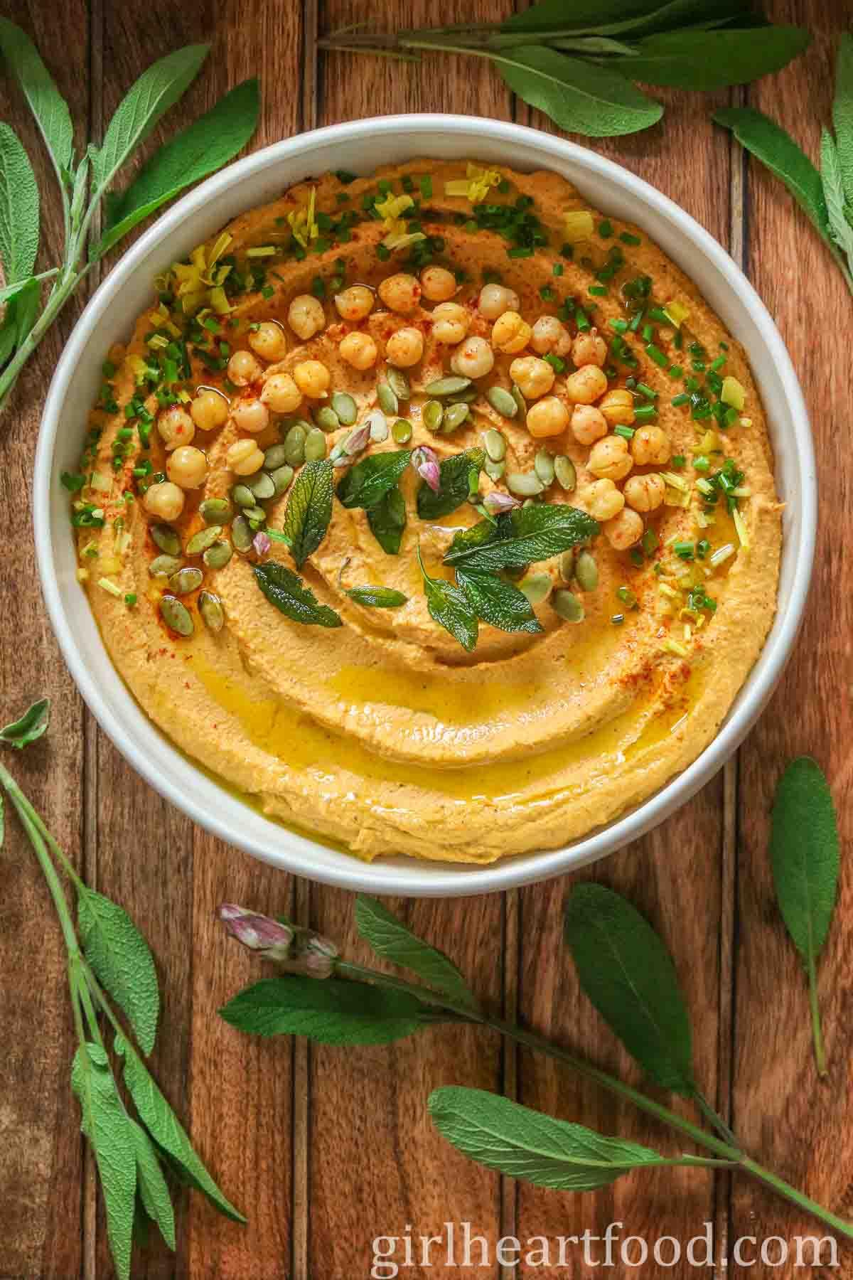 Round dish of garnished pumpkin-flavoured hummus alongside fresh sage.