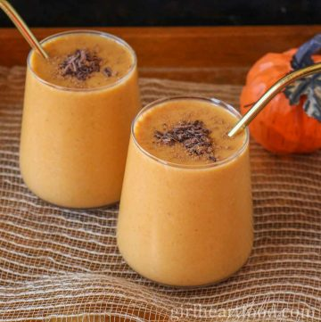 Two glasses of pumpkin smoothie garnished with chocolate, pumpkin pie spice and a gold straw.