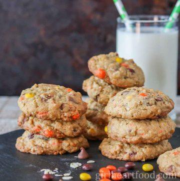 Stacks of Reese's candy cookies next to a glass of milk.