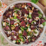 Large round dish of roasted beet salad with balsamic vinaigrette drizzled over top.
