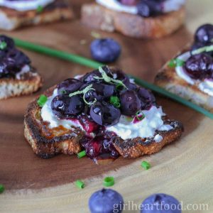 Roasted blueberry and goat cheese crostini garnished with lemon zest and chives and next to some berries.