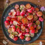 Black plate of roasted radishes garnished with chives.