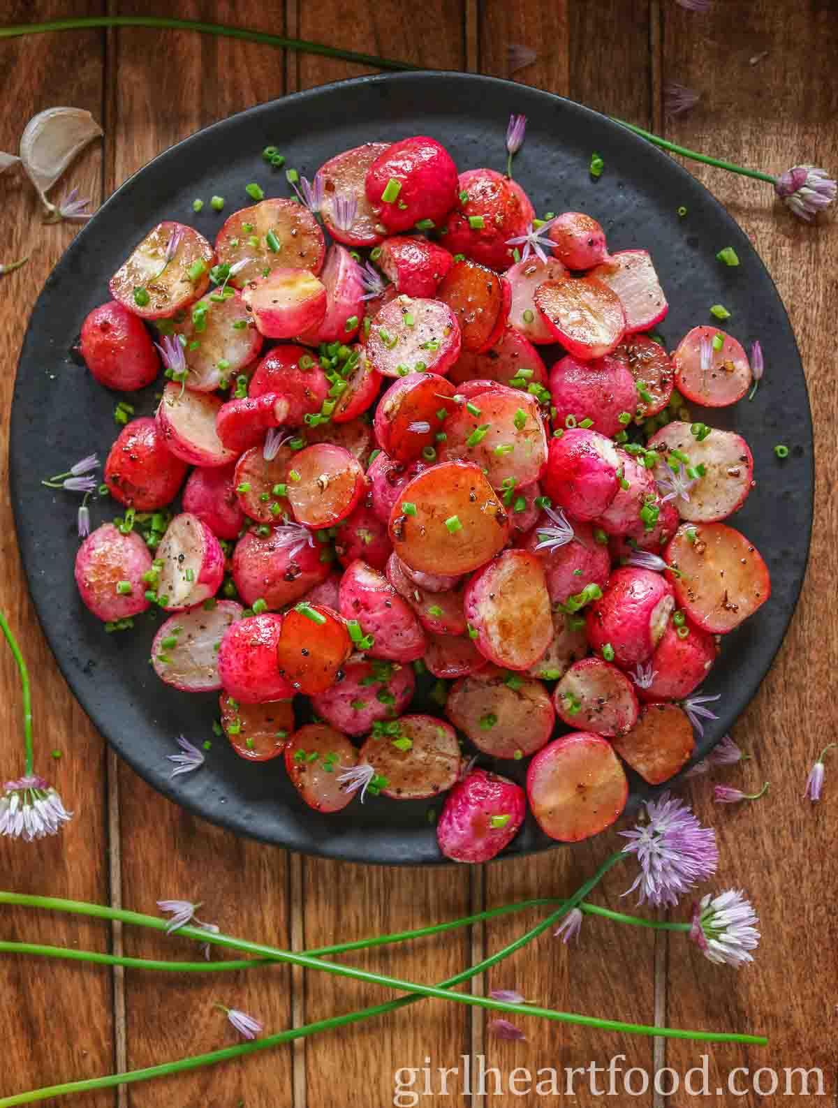 Black plate of roasted radishes alongside fresh chives.