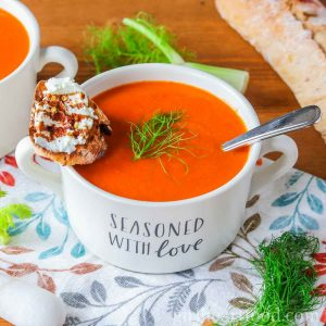 Bowl of roasted red pepper tomato soup with fennel garnished with fennel fronds and goat cheese crostino.