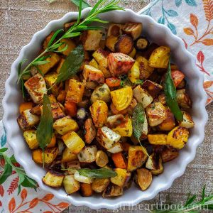 Round dish of a mixture of roasted root vegetables garnished with fresh herbs.
