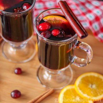 Glass of mulled wine with orange, cranberries and star anise and garnished with a cinnamon stick.