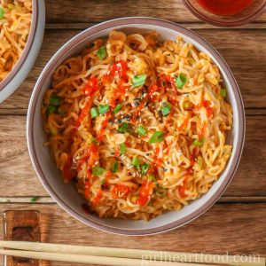 Bowl of spicy ramen noodles next to chopsticks.