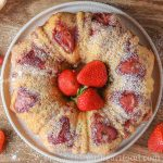 Strawberry bundt cake on a plate dusted with icing sugar and fresh strawberres in the centre.