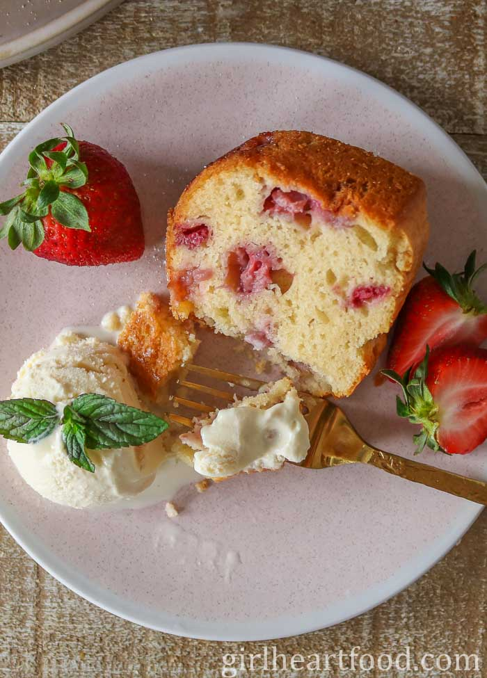 Piece of strawberry cake on a plate with ice-cream, fresh strawberries and a fork scooping some up.