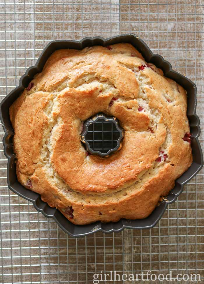 A cake in a Bundt pan on top of a cooling rack after being baked.