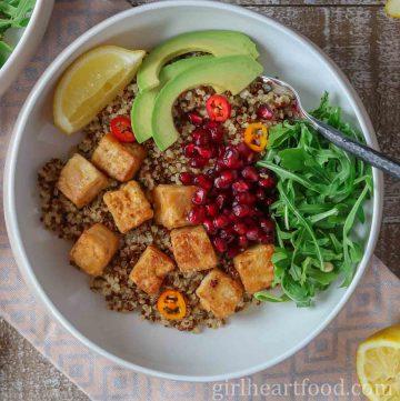 Bowl of cubes of crispy tofu, arugula, pomegranate, avocado and lemon over quinoa.
