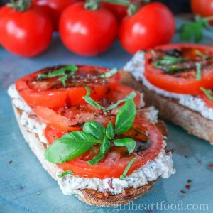 Slice of tomato ricotta toast garnished with balsamic vinegar and basil.