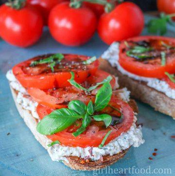 Slice of tomato ricotta toast garnished with balsamic vinegar and fresh basil.