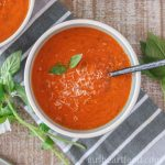Bowl of homemade tomato soup garnished with fresh basil and parmesan cheese.
