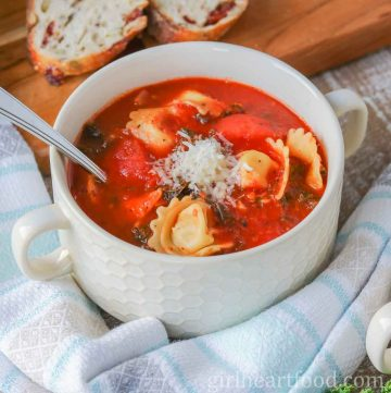 Bowl of tomato tortellini soup garnished with Parmesan cheese.