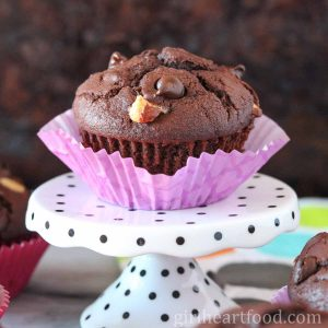 Triple chocolate muffin with purple liner on a polka dot stand.