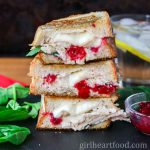 Tall stack of cheesy turkey cranberry sandwich next to spinach leaves and dish of cranberry sauce.