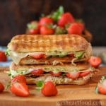 Two cheesy turkey panini sandwiches with strawberries stacked on top of each other.