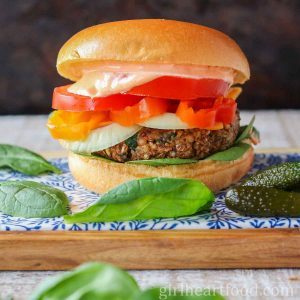 Garnished vegan lentil burger alongside baby spinach leaves and pickle.