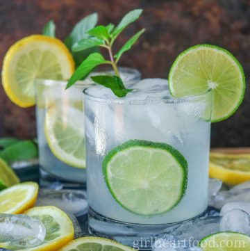 Two glasses of vodka soda garnished with lime and mint.