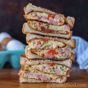 Stack of three western sandwich halves with eggs behind it.