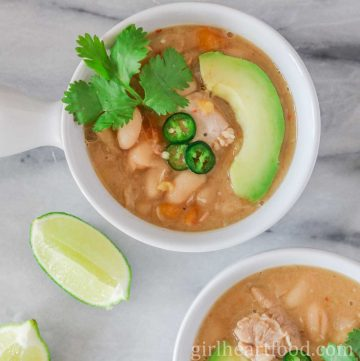 Bowl of white chicken chili garnished with hot pepper slices, avocado and cilantro.