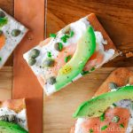 Close up of a goat cheese, avocado and smoked salmon appetizer on flatbread with capers, pepper and oil.