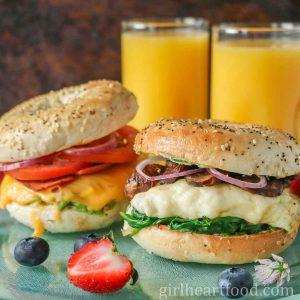 Two vegetarian bagel breakfast sandwiches next to berries and glasses of orange juice.