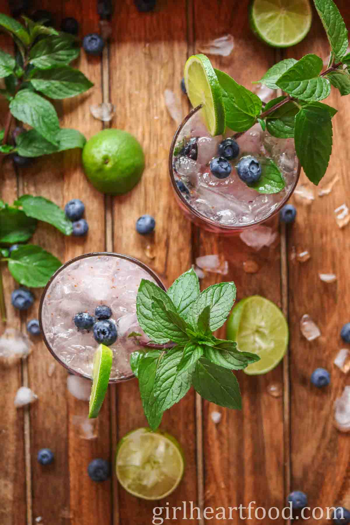 Overhead shot of two glasses of blueberry mojito drinks garnished with mint and lime.