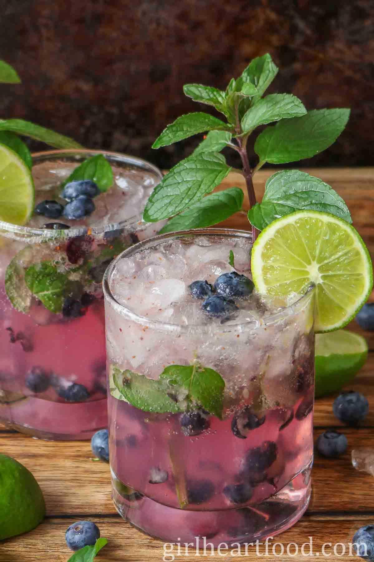 Two blueberry mojitos garnished with mint and lime.