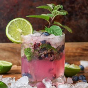 Glass of blueberry mojito garnished with mint and lime.