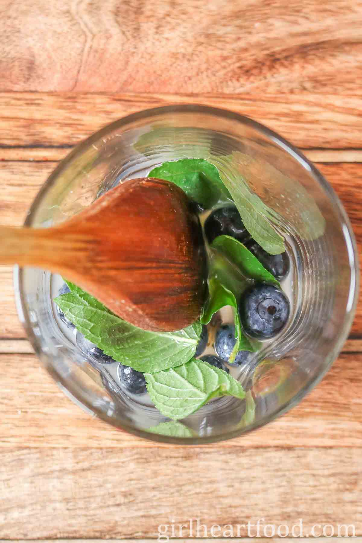 Wooden spoon in a glass with blueberries, mint and lime juice before being muddled.