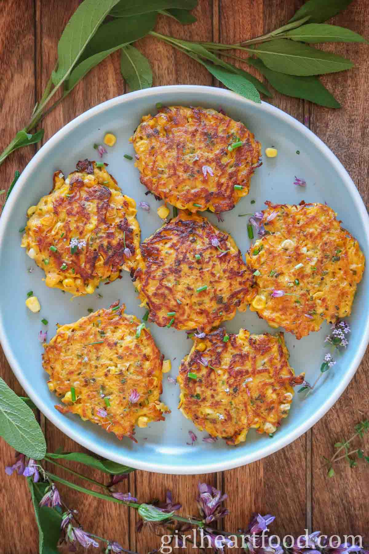 Six butternut squash corn fritters on a blue plate garnished with chives.