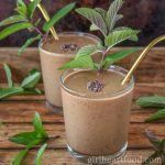 Two glasses of chocolate mint smoothie garnished with a mint sprig and cocoa nibs.